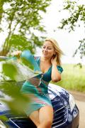 Photo of elegant woman sitting on the hood of car and looking at map Stock Photos