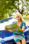 photo of elegant woman sitting on the hood of car and looking at map - stock photo