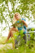 Photo of blond woman sitting by her car and looking at map Stock Photos
