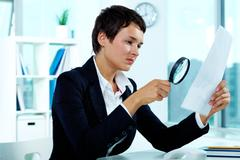 photo of pretty businesswoman looking at paper through spy glass - stock photo