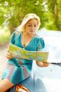 Photo of astonished blond woman sitting on the hood of her car and looking at ma Stock Photos