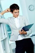 Photo of smart businesswoman looking through document in office Stock Photos