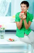 photo of happy young woman eating watermelon and looking at camera - stock photo