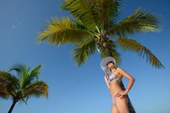 Woman in summer hat sunbathing under a palm tree on a background of blue sky Stock Photos