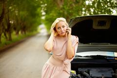 Photo of blond woman in trouble standing by her car and talking on cell phone Stock Photos