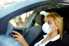 photo of blond female wearing respirator while driving car in polluted area - stock photo