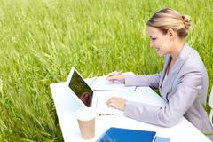 image of businesswoman in suit sitting in green grass and typing - stock photo
