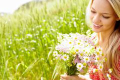 portrait of young woman holding bunch of flowers outside - stock photo