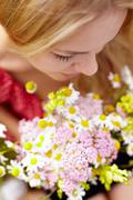 portrait of young woman holding bunch of chamomiles and smelling it - stock photo