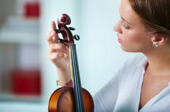 portrait of a young female tuning the violin - stock photo