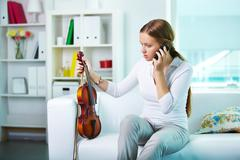 Portrait of a young female with the violin talking by phone Stock Photos