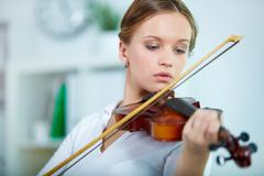portrait of a young female playing the violin - stock photo