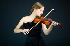 Portrait of a young female playing the violin Stock Photos