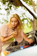 Photo of blond woman with wrench checking engine of her car Stock Photos