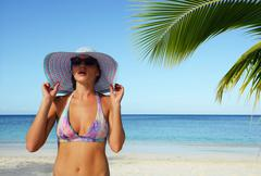 A woman in a summer hat stares into the distance, amid the ocean Stock Photos