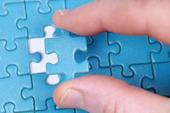 Fingers holding a puzzle piece Stock Photos