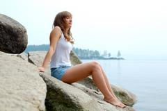 Portrait of pretty young lady having rest by the seaside Stock Photos
