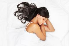 Portrait of a young brunette sleeping in bed Stock Photos