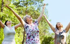 Stock Photo of portrait of three aged women with her arms raised and enjoy