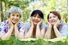 portrait of senior women resting on grass and looking at camera - stock photo