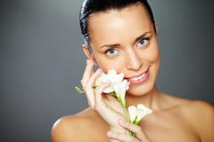 Stock Photo of gorgeous woman with white flower looking at camera with smile