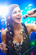portrait of a glamorous girl holding a mike and singing - stock photo