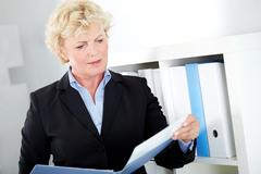 portrait of middle aged businesswoman reading paper in office - stock photo