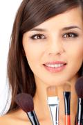 Portrait of a beautiful woman with several brushes Stock Photos