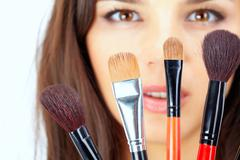 close-up of cosmetic brushes with female face in the background - stock photo