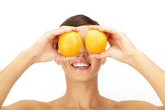 a young woman holding two oranges - stock photo