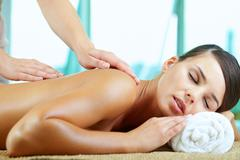 A young woman having pleasure during massage Stock Photos