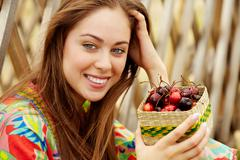 portrait of pretty girl holding cherries and looking at camera - stock photo