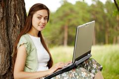 Stock Photo of image of pretty female working with laptop on summer day