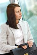 Portrait of smiling businesswoman with briefcase looking through window Stock Photos