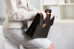 close-up of businesswoman holding briefcase - stock photo