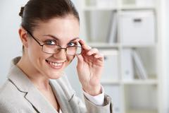 portrait of successful businesswoman looking at camera through eyeglasses - stock photo