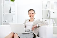 Portrait of smiling businesswoman with laptop looking at camera in office Stock Photos