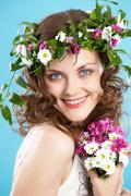 Stock Photo of beautiful woman in floral wreath looking at camera with smile