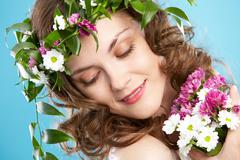 Beautiful woman in floral wreath looking aside Stock Photos
