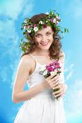 beautiful woman with bunch of flowers looking at camera with smile - stock photo