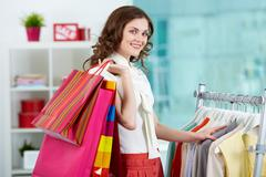 portrait of pretty woman with colorful bags looking at camera in clothing depart - stock photo