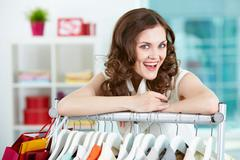 portrait of happy woman looking at camera in clothing department - stock photo
