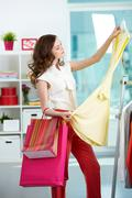 portrait of pretty woman choosing new dress in clothing department - stock photo