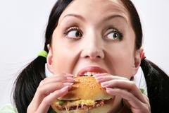 image of hungry girl eating hamburger and looking aside - stock photo