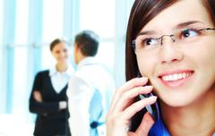 Photo of smart businesswoman calling with interacting people behind Stock Photos