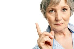 Photo of elderly female with her forefinger pointed upwards on white background Stock Photos