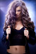 Portrait of a girl with wavy hair against blue background Stock Photos