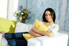 portrait of brunette with pillow sitting on sofa and looking at camera - stock photo