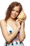 portrait of a young girl holding a shell, looking at camera and smiling - stock photo