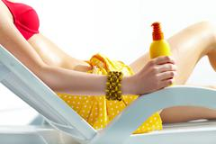 close-up of a girl's hand holding sunscreen - stock photo